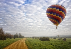 hot air balloon above a country road