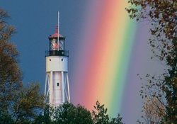 background with rainbow lighthouse at sea