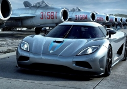 koenigsegg at an airport of old mig planes
