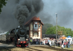 steam train coming into a polish station